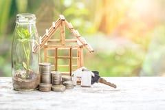 Münzenstapel Einsparungensgeld von Münzen, Musterhaus mit Schlüsselhauskonzept für Eigentumsleiter, Hypothek und Immobilien inves lizenzfreies stockfoto