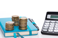 Münzenstapel, -Taschenrechner und -notizbuch Lizenzfreies Stockbild