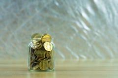 Münzgeld im Glasgefäß auf Tabelle, für die Rettung und das Ein Bankkonto haben der Flosse Lizenzfreie Stockfotografie