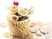 Münzsammlung im handgemachten Korb Lizenzfreie Stockfotos