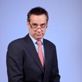 Mürrischer die Stirn runzelnder verärgerter Geschäftsmann auf Blau lizenzfreie stockfotos