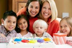 Mütter, die den Geburtstag des Kindes mit Freunden feiern Stockfotos