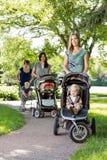 Mütter, die Kinderwagen im Park drücken Stockfotos