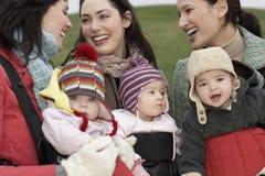 Mütter mit Babys in den Riemen am Park lizenzfreies stockbild