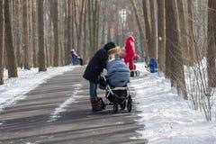 Mütter mit Spaziergängern auf einem Weg im Park im Winter Lizenzfreies Stockfoto