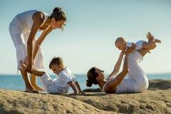 Mütter und ihre Söhne tun Yogaübungen an der Küste lizenzfreie stockfotografie