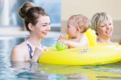 Mütter und Kinder, die den Spaß zusammen spielt mit Spielwaren im Pool haben Lizenzfreie Stockfotografie