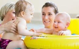 Mütter und Kinder, die den Spaß zusammen spielt mit Spielwaren im Pool haben Lizenzfreie Stockfotos