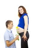 Mąż daje kwiatowi ciężarnemu obrazy stock
