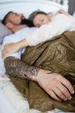 Mąż i żona śpi wpólnie w jeden łóżku - tatuującego mężczyzny ręka obrazy stock