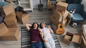 Mąż i żona opowiada wewnętrznego lying on the beach na podłodze w nowym domu wokoło pudełek zbiory