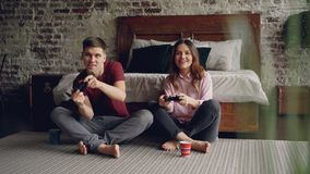Mąż i żona siedzi na sypialni podłoga w domu bawić się gra wideo mienia joysticki, mężczyzna wygrywa i kobieta jest zbiory
