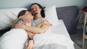Mąż i żona w piżamach opowiada przytulenie w łóżku w sypialni w domu zdjęcie wideo