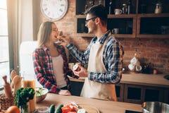 Mąż karmi żonie banana na kuchni Obraz Stock