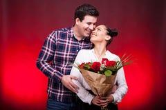 Mąż obejmuje jej żony podczas gdy trzyma róża bukiet w brzęczeniach Obraz Stock