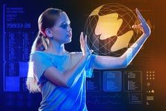 Mądra dziewczyna patrzeje Ziemskiego hologram podczas gdy trzymający je zdjęcie stock