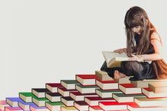 Mądry mały śliczny dziewczyna dzieciak w czarnym smokingowym obsiadaniu na stosie książkowy czytanie, uczenie informacja i wiedza fotografia stock
