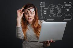 Mądry pracownik stawia jej szkła up podczas gdy trzymający laptop fotografia stock