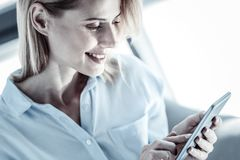Mądrze ładna kobieta uśmiecha się jej smartphone i używa zdjęcie royalty free