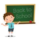 Mądrze chłopiec przedstawia coś przed blackboard Zdjęcie Royalty Free