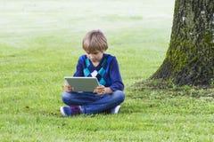 Mądrze chłopiec używa pastylkę outdoors Technologia, styl życia, edukacja, ludzie pojęć Zdjęcia Stock