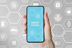 Mądrze domowej automatyzaci pojęcie z ręką trzyma nowożytnego bezpłatnego smartphone przed neutralnym tłem z ikonami applianc Obrazy Royalty Free