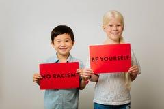 Mądrze dzieci trzyma stoły przeciw rasizmowi w ich rękach zdjęcie stock