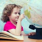 Mądrze małych dziewczynek spojrzenia blisko na kule ziemskie Zdjęcie Stock