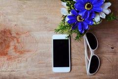 Mądrze okulary przeciwsłoneczni z kwiatem na starym drewnianym stole i telefon Obrazy Royalty Free