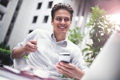 Mądrze postawa Pozytywny przystojny mężczyzna używa laptop w kawiarni i obsiadanie sieci konferencję podczas gdy surfujący intern obrazy royalty free