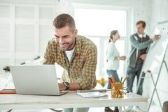 Mądrze pozytywny mężczyzna pisać na maszynie na jego laptopie zdjęcie stock