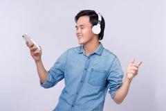 Mądrze przypadkowy azjatykci mężczyzna słucha muzyka w pracownianym tle zdjęcia stock