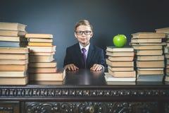 Mądrze szkolnej chłopiec obsiadanie przy stołem z dużo rezerwuje Zdjęcia Stock