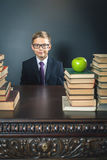 Mądrze szkolnej chłopiec obsiadanie przy stołem z dużo rezerwuje Obraz Royalty Free
