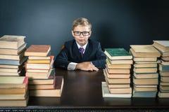 Mądrze szkolnej chłopiec obsiadanie przy stołem z dużo rezerwuje Obrazy Royalty Free