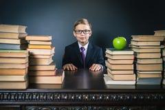 Mądrze szkolnej chłopiec obsiadanie przy stołem z dużo rezerwuje Fotografia Stock
