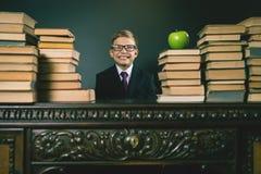 Mądrze szkolnej chłopiec obsiadanie przy stołem z dużo rezerwuje Obrazy Stock