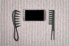 Mądrze telefon między hairbrushes Obraz Royalty Free