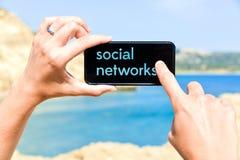 Mądrze telefon trzymający kobietą przy morzem z ogólnospołecznymi sieciami Obraz Royalty Free