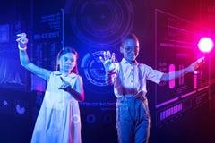 Mądrzy dzieciaki używa futurystycznych przyrząda podczas gdy studiujący zdjęcie stock