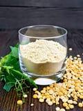 Mąka groch w glassful na zmrok desce obraz stock