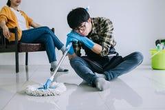 Męża housekeeping i cleaning pojęcie, męczący mężczyzna wyciera pył w błękitnych gumowych rękawiczkach używać kwacz podczas gdy c obraz stock