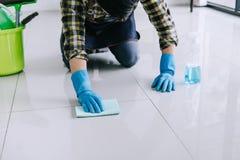 Męża housekeeping i czyści pojęcie, Szczęśliwy młody człowiek wyciera pył w błękitnych gumowych rękawiczkach używać kiść i duster zdjęcie royalty free