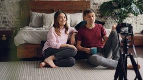 Męża i żony bloggers nagrywają wideo vlog, macha ręki i gestykulujący, opowiadający i śmiający się, używają zbiory wideo