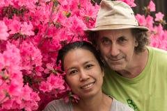 Męża i żony pozycja przed różową azalią kwitnie w tshirt na gorącej wiosny dniu obraz royalty free