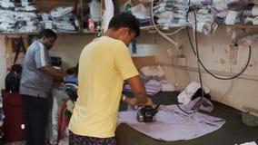 Mężczyźni odprasowywają białe koszula z elektrycznymi parowymi żelazami w warsztacie zdjęcie wideo