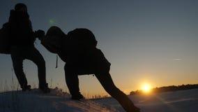 Mężczyźni pomagają each inny podbijać szczyt wysoka śnieżna góra trzymać ręki i rozciągać each inny nakrywać przy zbiory