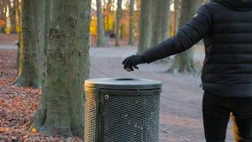 Mężczyzn rzutów grat w koszu na śmieci w parku zbiory