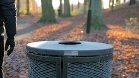 Mężczyzn rzutów grat w koszu na śmieci w parku zbiory wideo