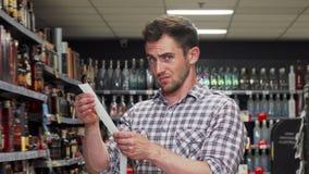 Mężczyzn spojrzenia dewastujący po płacić zakupy rachunek przy supermarketem zdjęcie wideo